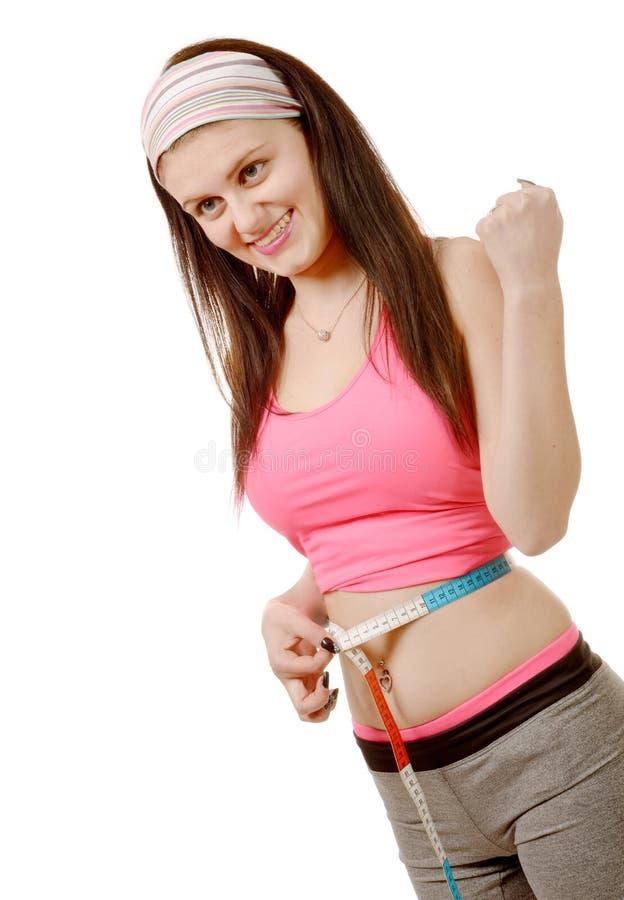 Jong meisje die maatregel maken rond haar taille met het meten van band stock foto