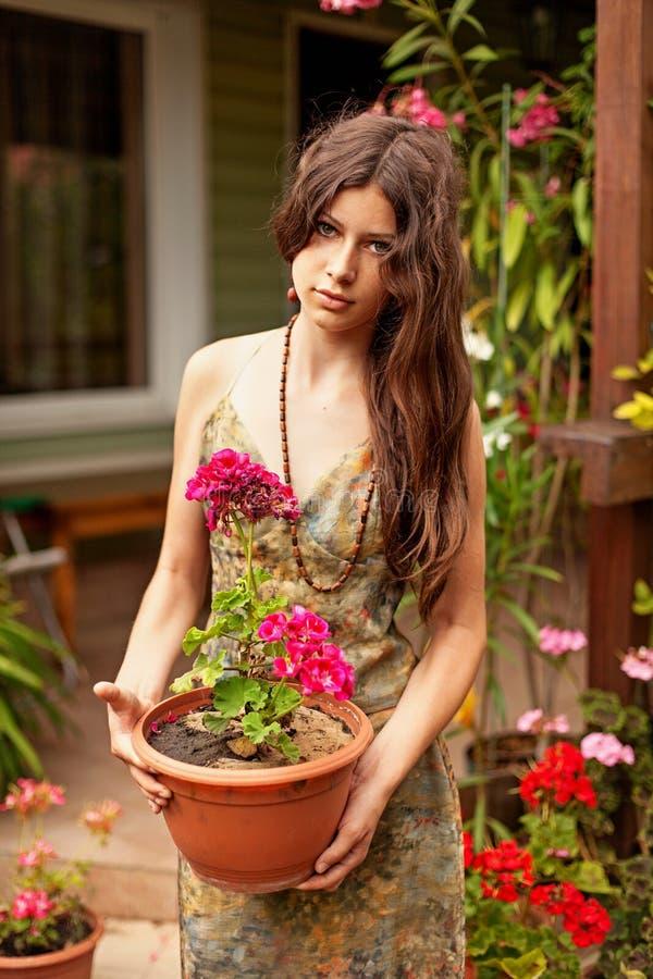 Jong meisje die met lang bruin haar een pot van geraniums houden royalty-vrije stock afbeelding