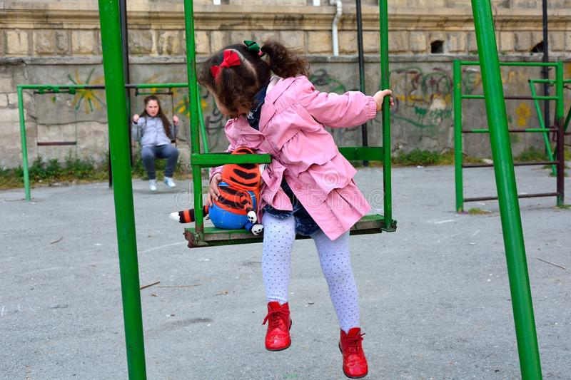 Jong meisje die met stuk speelgoed op schommeling terug grote zuster bekijken royalty-vrije stock afbeelding
