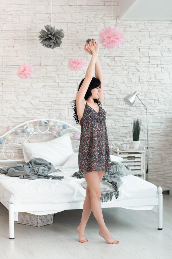 Jong meisje die ochtendoefeningen in slaapkamer doen stock fotografie