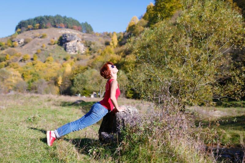 Jong meisje die oefeningen op de rivierkust doen tegen de achtergrond van bergen en bos stock foto
