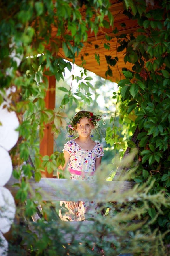 Jong meisje die op een groene veranda glimlachen royalty-vrije stock foto's