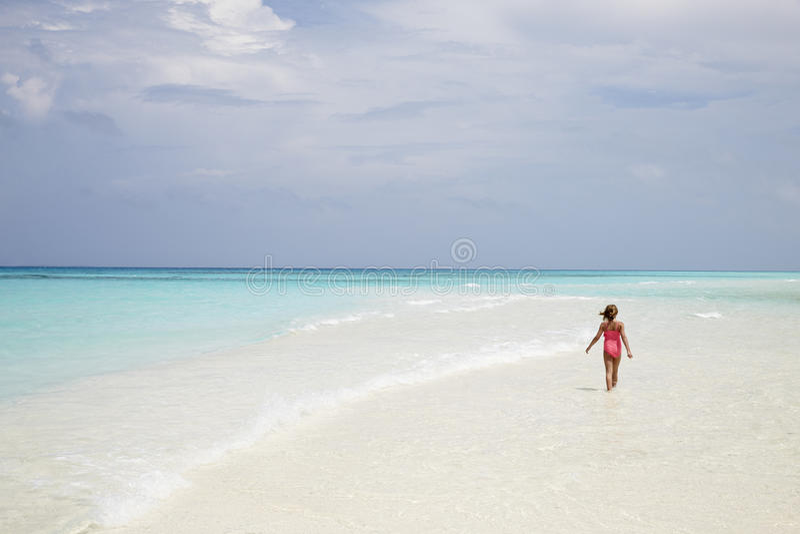 Jong meisje die op een leeg wit zandstrand lopen, achtermening stock foto's
