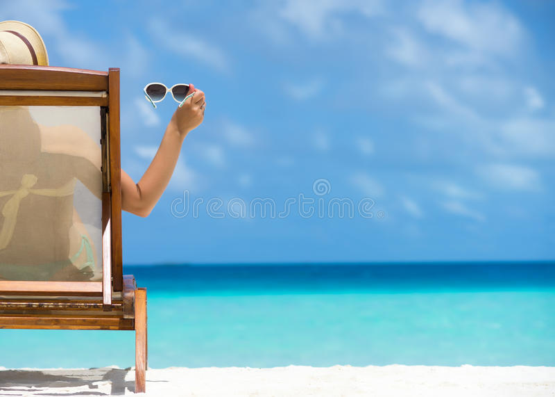 Jong meisje die op een strandlanterfanter liggen met in hand glazen royalty-vrije stock afbeelding