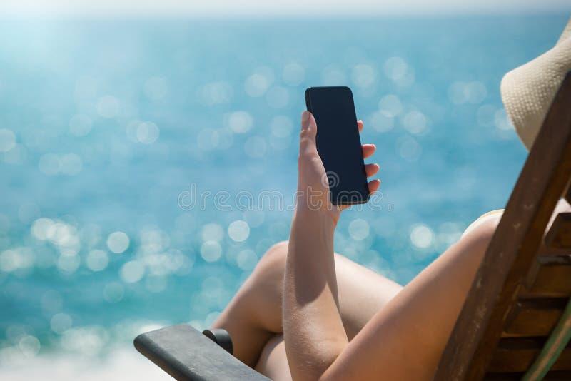 Jong meisje die op een strandlanterfanter liggen met mobiele in hand telefoon stock foto's