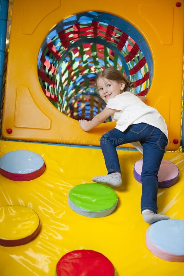 Jong meisje die op helling in tunnel op zacht spelcentrum beklimmen royalty-vrije stock foto