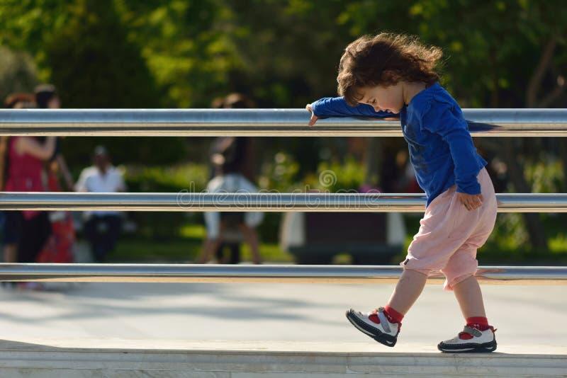 Jong meisje die op het metaaltraliewerk van de muurholding lopen stock foto's