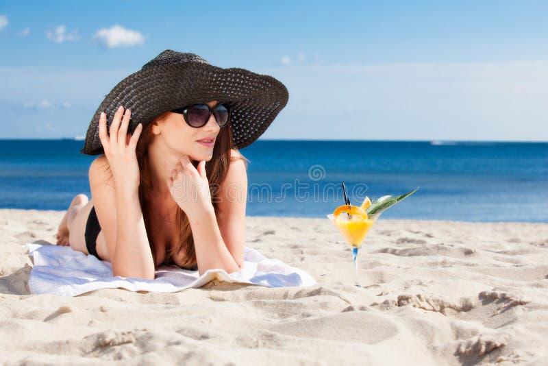 Jong meisje die op het strand liggen stock fotografie