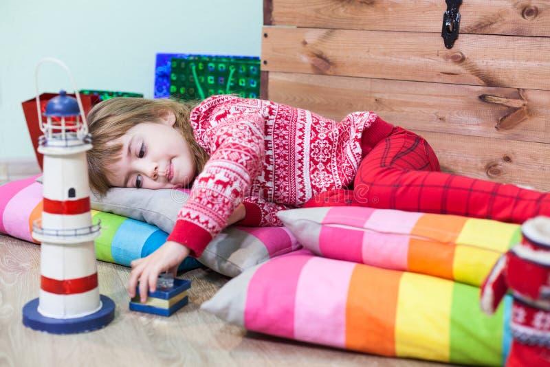 Jong meisje die op vloer en het spelen speelgoed, vermoeid kind leggen stock foto's