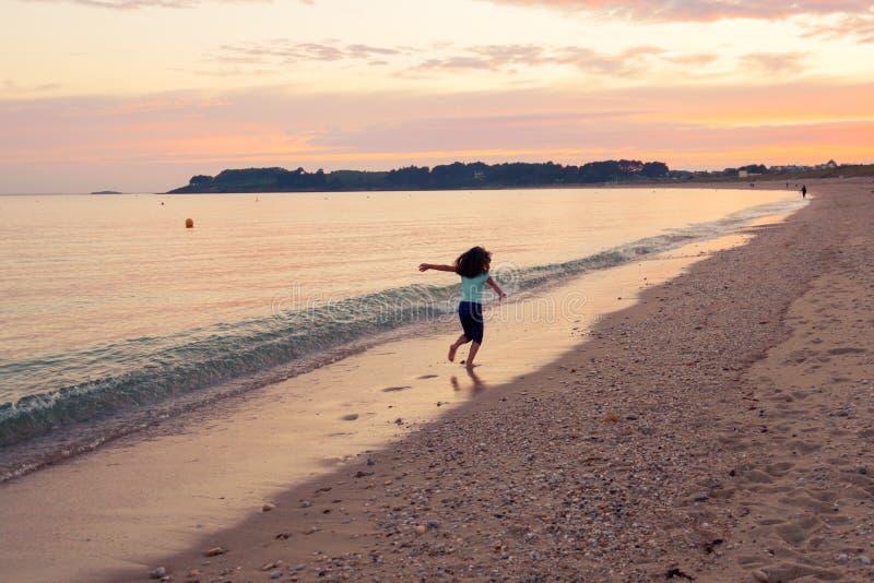 Jong meisje die op zonsondergang overzeese achtergrond weggaan stock foto's