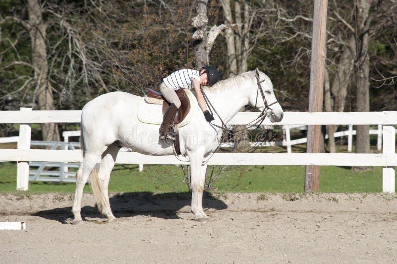 Jong meisje die paard koesteren bij het berijden les royalty-vrije stock foto