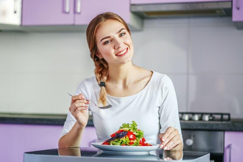 Jong meisje die plantaardige salade in de keuken eten Het concept is royalty-vrije stock fotografie