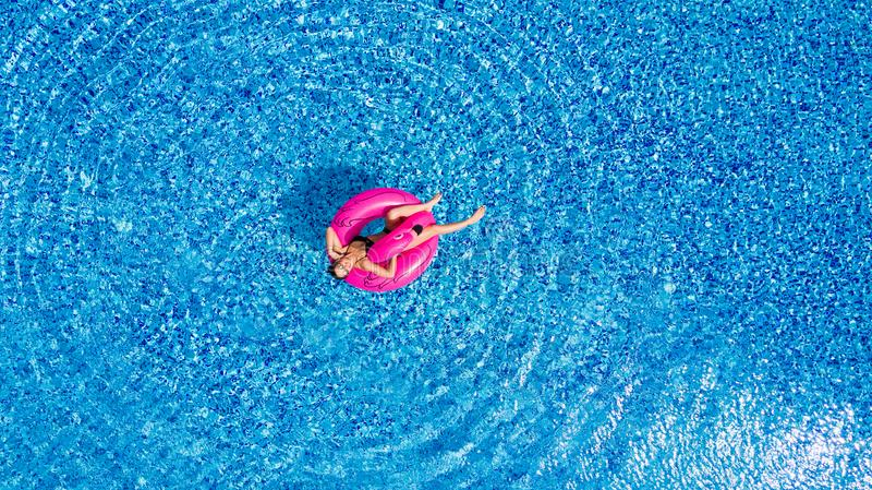 Jong meisje die pret hebben en en pret in de pool op een opblaasbare roze flamingo in een badpak in de zomer van abov hebben lach royalty-vrije stock afbeelding