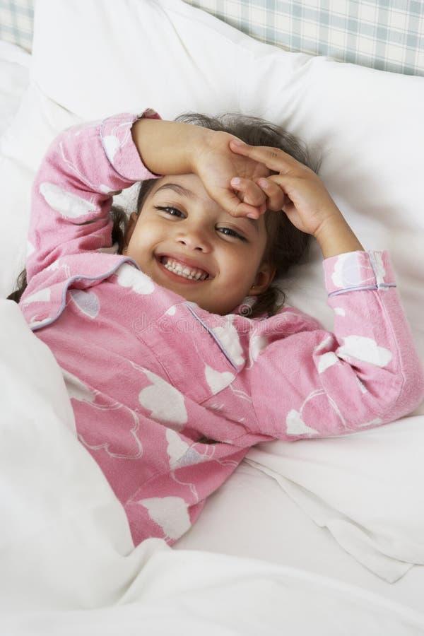 Jong Meisje die Pyjama's dragen die in Bed liggen royalty-vrije stock afbeelding