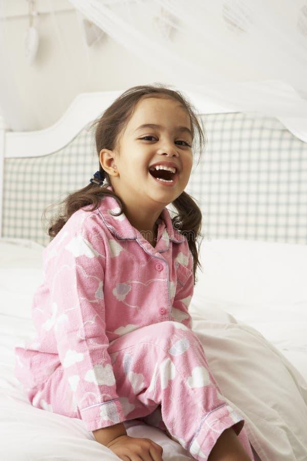 Jong Meisje die Pyjama's dragen die op Bed zitten royalty-vrije stock afbeelding