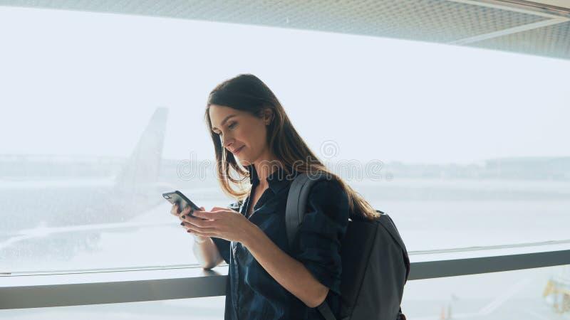 Jong meisje die smartphone gebruiken dichtbij luchthavenvenster De gelukkige Europese vrouw met rugzak gebruikt mobiele app in te stock afbeelding