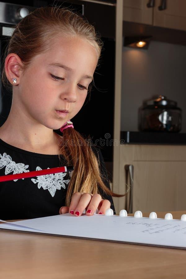 Jong meisje die terwijl het doen van thuiswerk bij het de holdingspotlood van de keukenlijst denken stock afbeeldingen