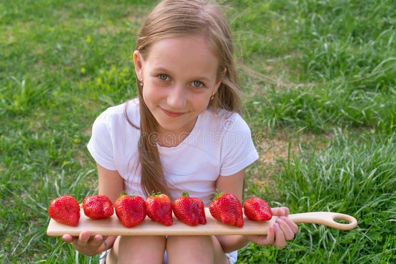 Jong meisje die twee verse sappige aardbeien in handen houden royalty-vrije stock afbeeldingen