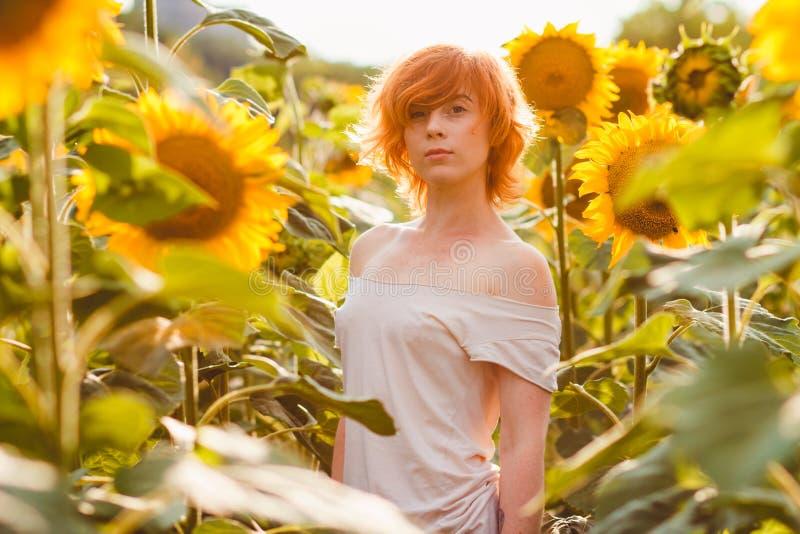 Jong meisje die van aard op het gebied van zonnebloemen genieten bij zonsondergang, portret van het mooie redheaded vrouwenmeisje royalty-vrije stock foto