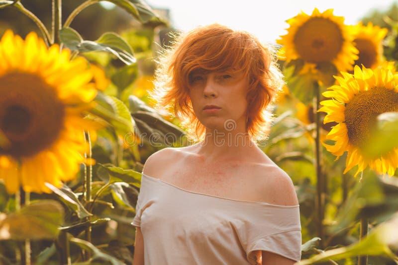 Jong meisje die van aard op het gebied van zonnebloemen genieten bij zonsondergang, portret van het mooie redheaded vrouwenmeisje stock fotografie
