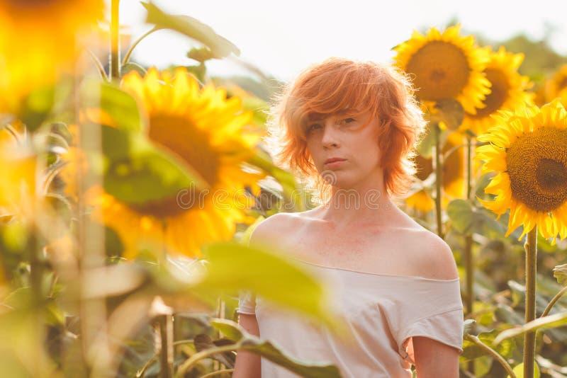 Jong meisje die van aard op het gebied van zonnebloemen genieten bij zonsondergang, portret van het mooie redheaded vrouwenmeisje stock foto's