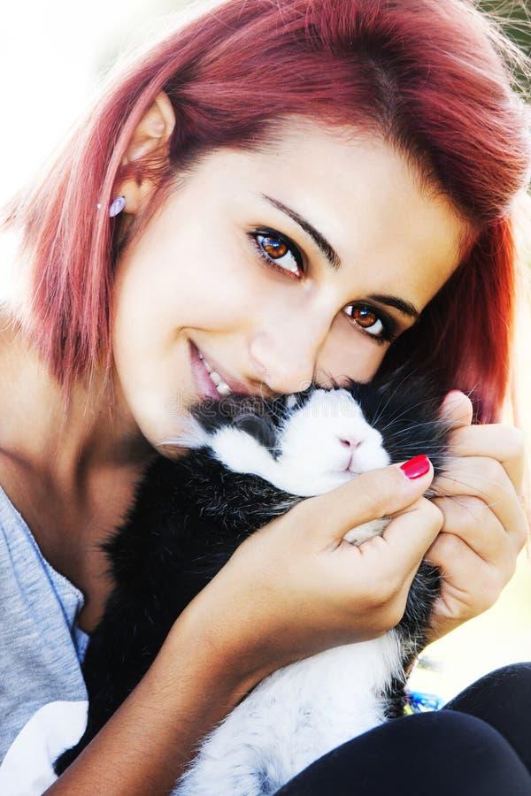 Jong meisje die van haar konijntje houden Het koesteren en het kussen stock foto's