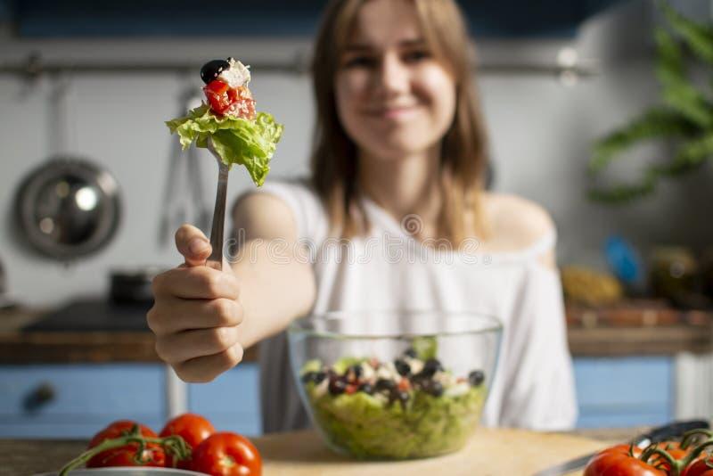 Jong meisje die vegetarische salade thuis in de keuken eten, probeert zij gezond voedsel bij de houten lijst royalty-vrije stock afbeelding