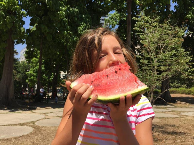 Jong meisje die watermeloen in openlucht eten stock fotografie