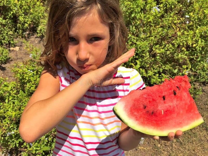 Jong meisje die watermeloen in openlucht eten stock afbeelding