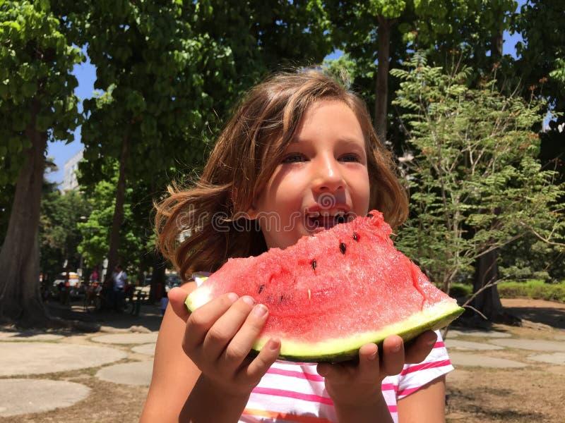 Jong meisje die watermeloen in openlucht eten stock afbeeldingen