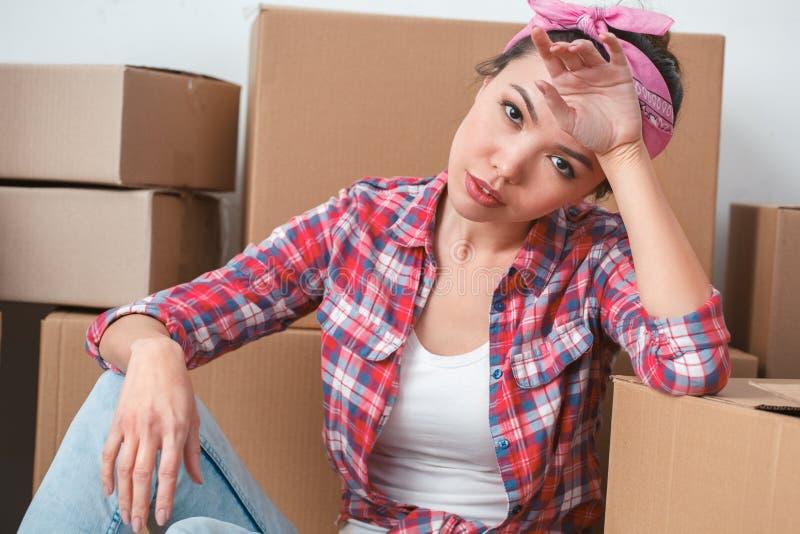 Jong meisje die zich aan nieuwe plaatszitting bewegen die op vermoeide doos leunen stock afbeelding