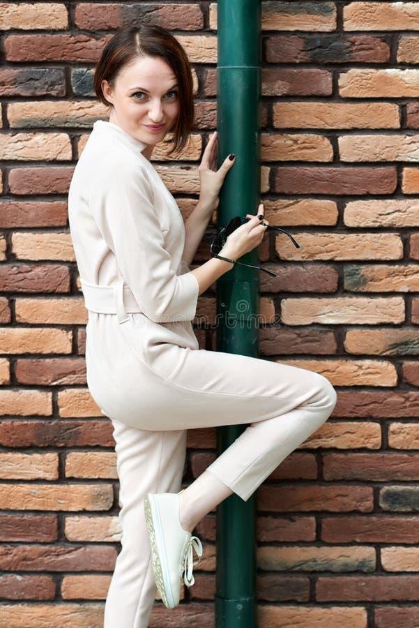 Jong meisje die zich bij de bruine bakstenen muur en de groene buis in de straat bevinden en pret hebben royalty-vrije stock afbeelding