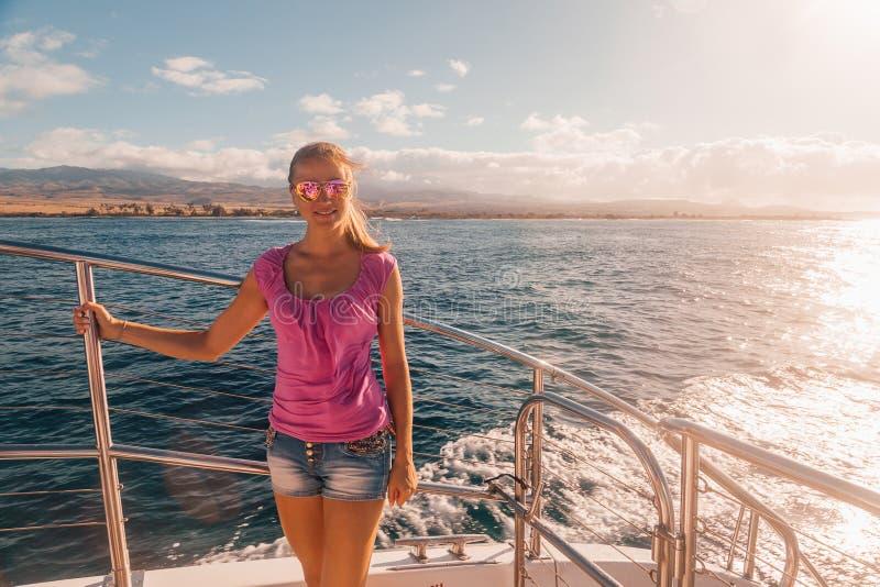 Jong meisje die zich op de boot dichtbij het eiland van Kauai bevinden stock foto's