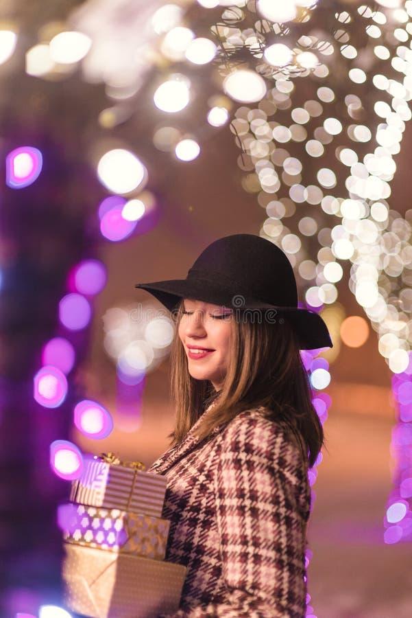 Jong meisje die zich vooraan op de lichten bevinden die van de Kerstmisboom PR houden royalty-vrije stock afbeeldingen