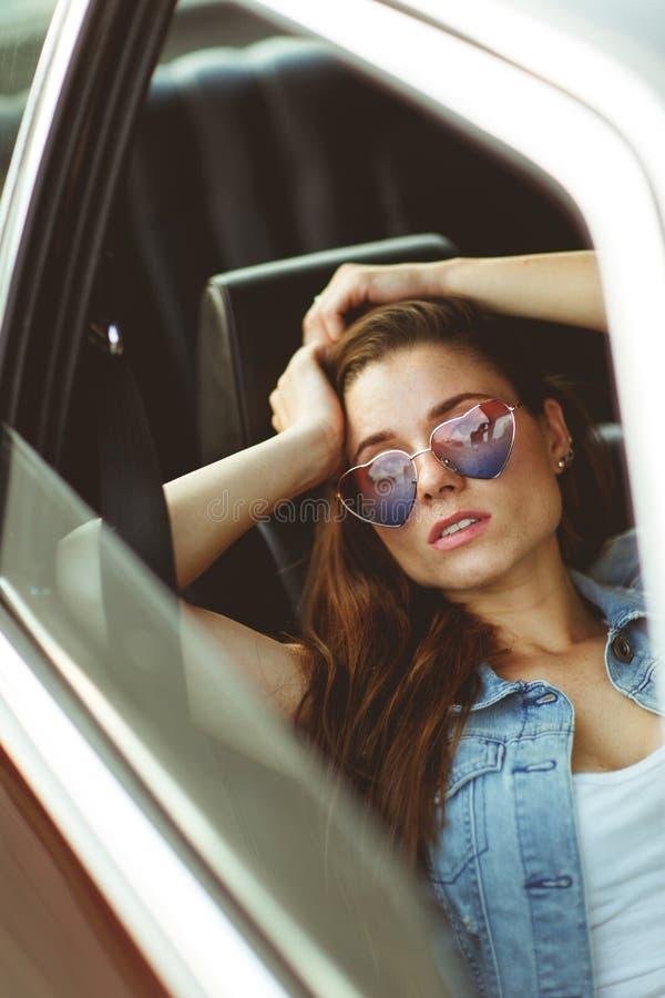 Jong meisje die in zonnebril in auto, gekleurde foto zitten stock afbeeldingen