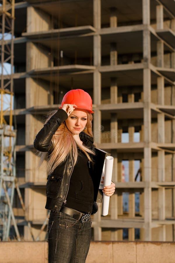 Jong meisje in een helm vóór de bouw stock foto's