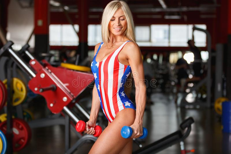 Jong meisje in een sportieve bikinitribunes met een domoor Binnen de gymnastiek royalty-vrije stock afbeeldingen