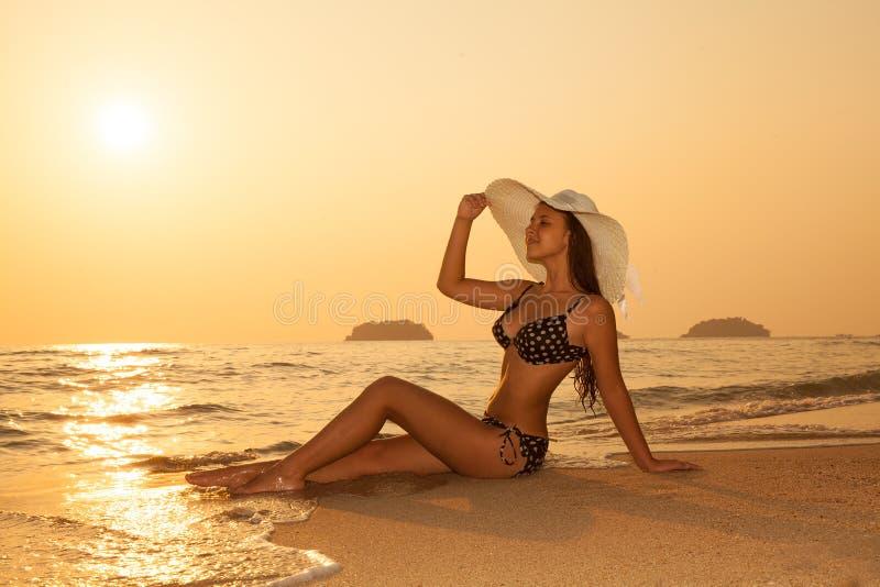 Jong meisje in een strohoed op een tropisch strand bij zonsondergang De zomer royalty-vrije stock foto