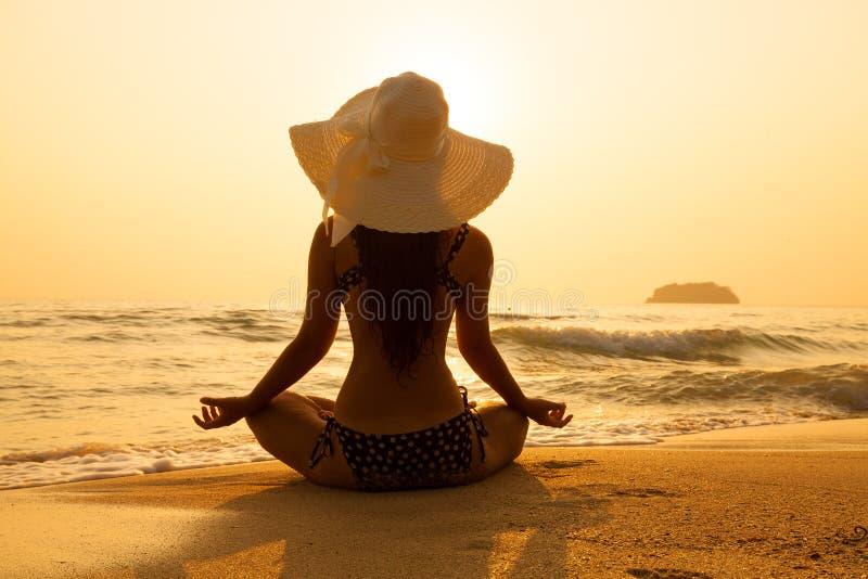 Jong meisje in een strohoed op een tropisch strand bij zonsondergang De zomer stock afbeelding