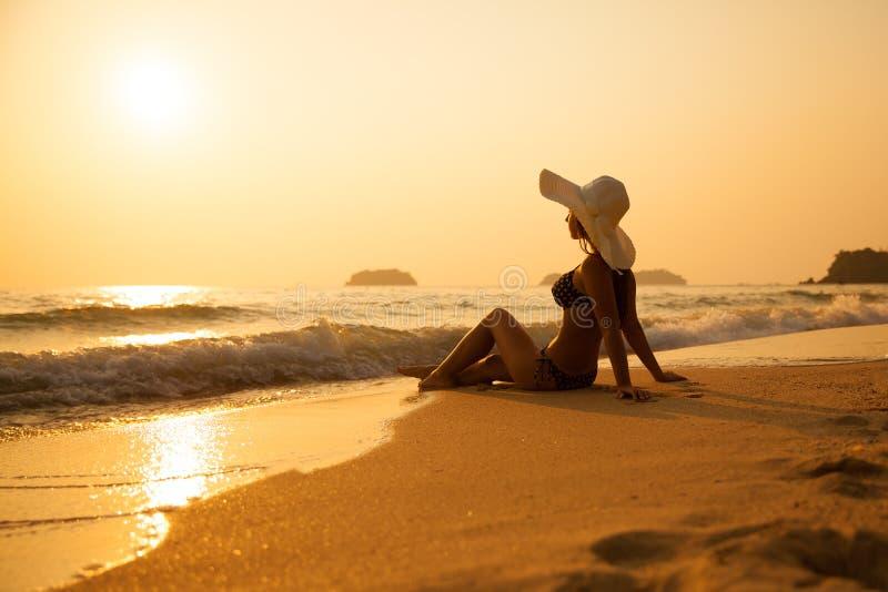 Jong meisje in een strohoed op een tropisch strand bij zonsondergang De zomer stock foto's