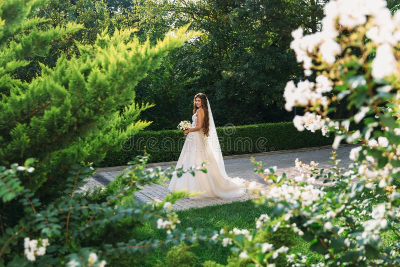Jong meisje in een witte kleding in de weide Vrouw in het mooie lange kleding stellen in de tuin Overweldigende bruid in a royalty-vrije stock foto's