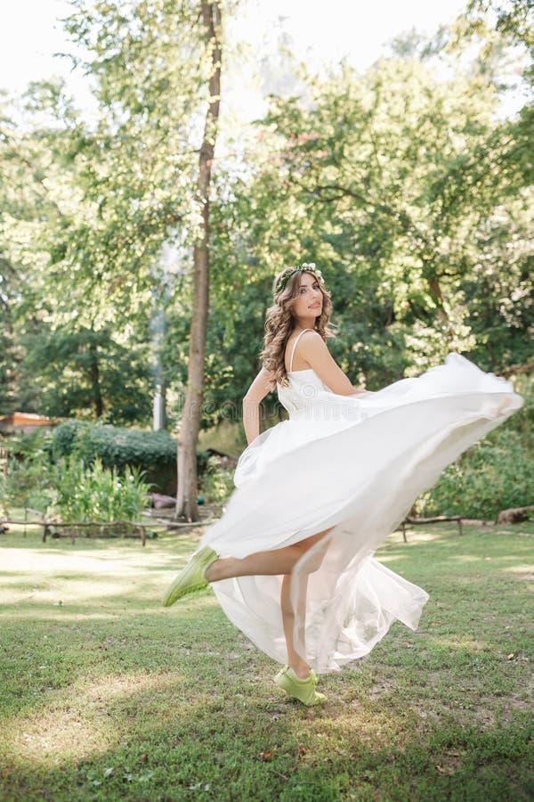 Jong meisje in een witte kleding in de weide Vrouw in het mooie lange kleding stellen in de tuin Overweldigende bruid in een huwe stock foto's
