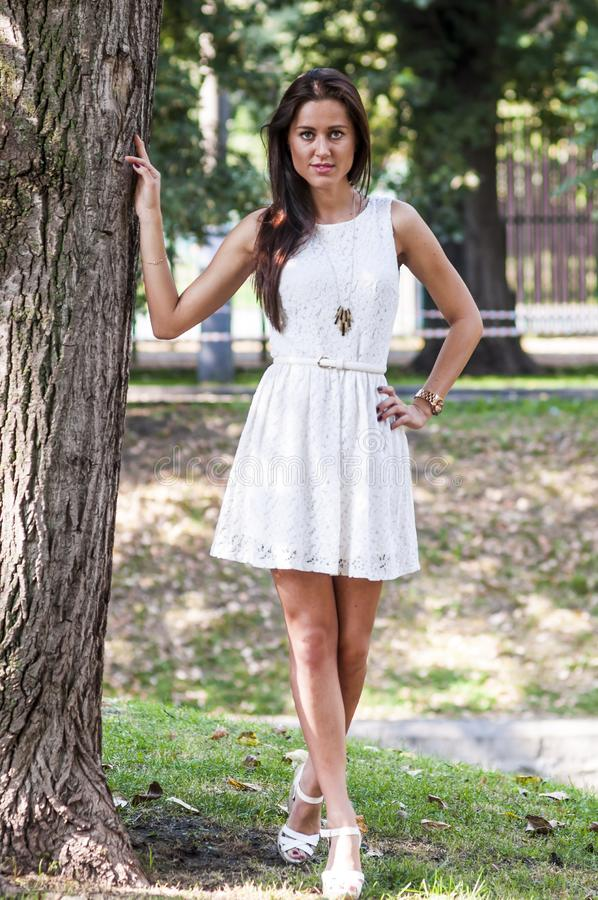 Jong meisje in een witte kleding in een de zomerpark stock foto's