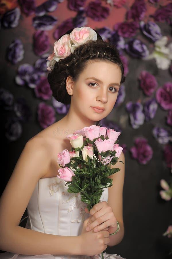 Jong meisje in een witte kleding met roze rozen royalty-vrije stock fotografie