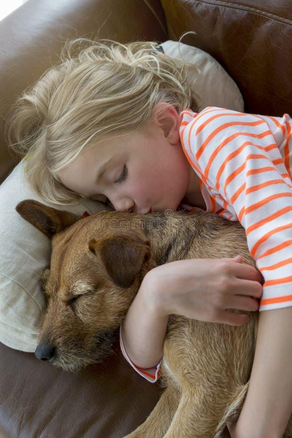 Jong meisje en haar hond die thuis knuffelen stock foto's