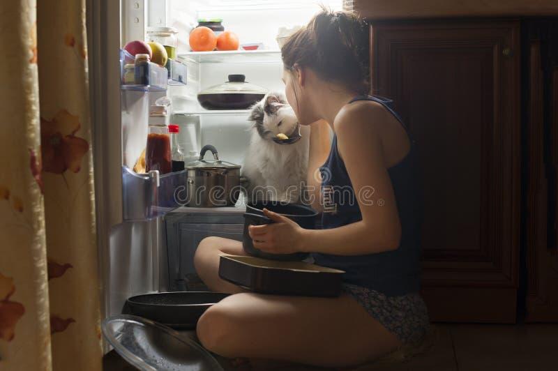 Jong meisje en haar pluizige kat die bij nacht eten royalty-vrije stock fotografie