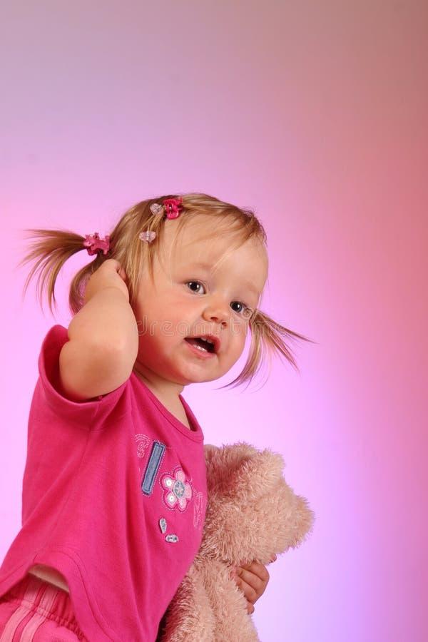 Jong meisje en haar teddybeer in roze royalty-vrije stock foto's