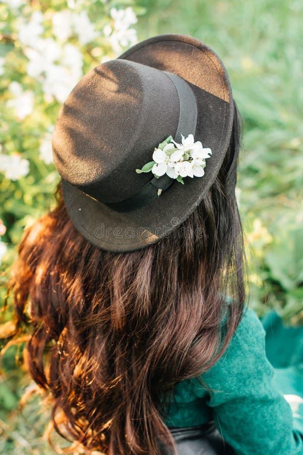 Jong meisje in groene kleding en zwarte hoed stock fotografie