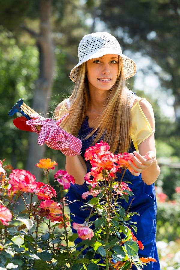 Jong meisje in het eenvormige werken met rozen royalty-vrije stock foto