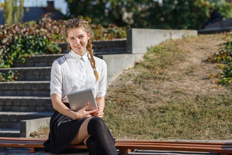 Jong meisje in het park met een in hand tablet stock afbeelding